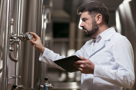 brewery: Serious man working in brewery Stock Photo