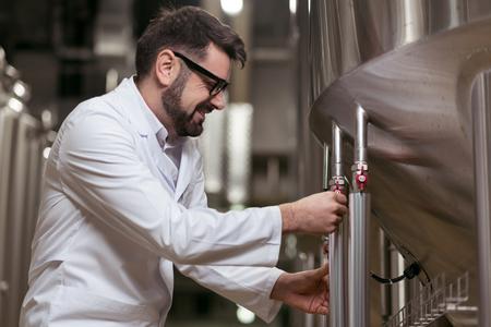 brasserie: Handsome man using brewing machine