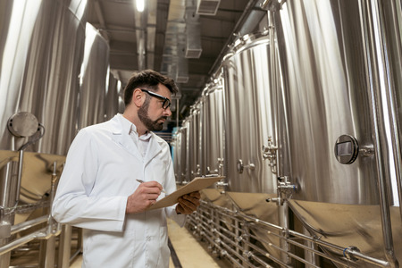 brewery: Concentrated man making notes in brewery Stock Photo
