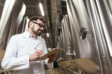 brewery: Smiling man making notes in brewery Stock Photo