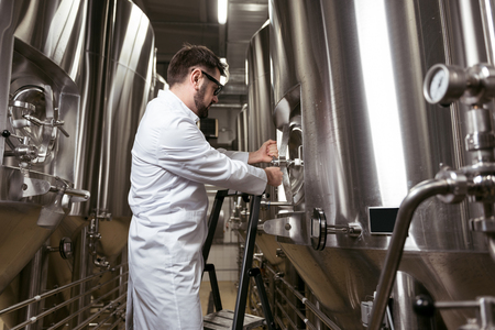 brasserie: Concentrated man using ladder in brewery