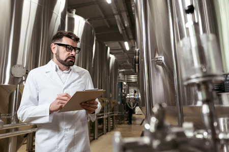 brewery: Serious man making notes in brewery Stock Photo