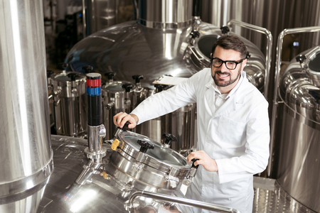 brasserie: Smiling man using brewing mechanism at factory Stock Photo
