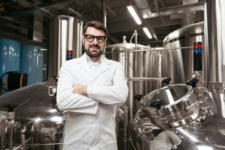 overjoyed: Overjoyed man standing at beer factory Stock Photo