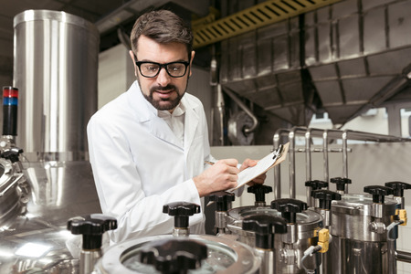 brasserie: Concentrated man noting work results on beer factory Stock Photo