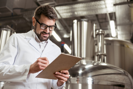 brasserie: Smiling man making notes at beer factory