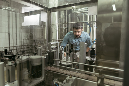 concentrated: Concentrated man controlling products on brewing factory