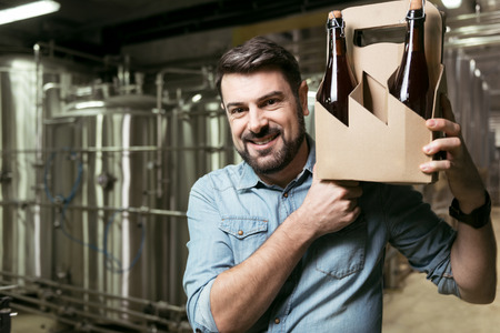 overjoyed: Overjoyed man holding bottles of alcohol in brewery Stock Photo