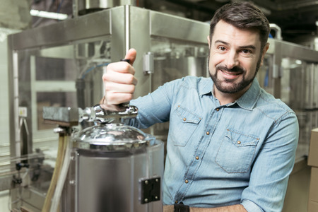 brewery: Delighted man pouring alcohol in brewery