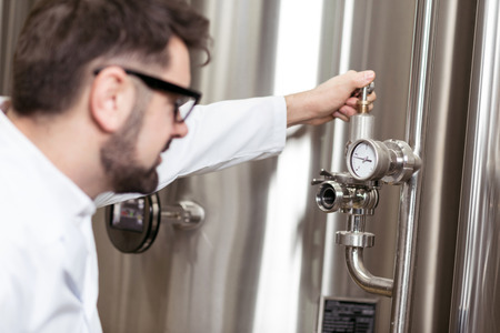 brasserie: Happy man using mechanism on brewing factory