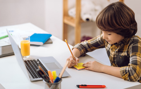 Clever boy writing notes with pensil. Stock Photo