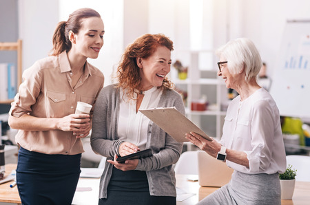 opinions: Lively positive businesswomen sharing opinions in the office