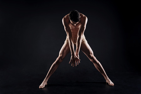 Slim concentrated athlete stretching in the studio