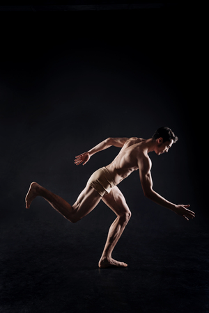 Muscular athlete posing in the dark lighted studio