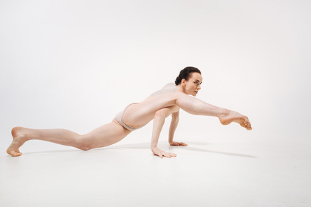 Flexible young ballet dancer stretching in the studio