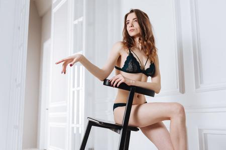 Pretty woman in lingerie sitting in studio