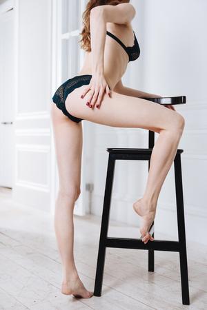Pretty girl in underwear touching her leg Stock Photo