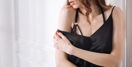 Beautiful woman with perfect skin touching her shoulder