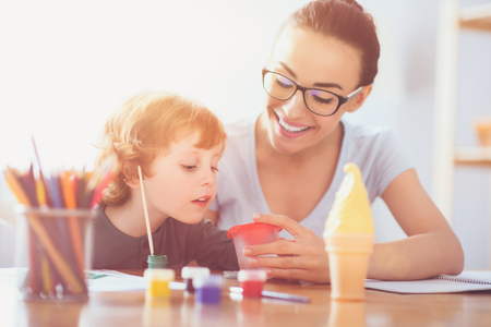 Young mother and her toddler son painting together Stock Photo