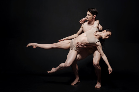 Involved ballet dancers performing together in the studio