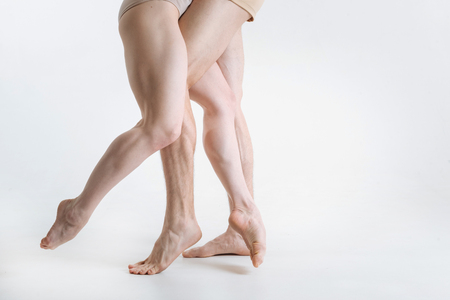 Tensed ballet dancers legs performing in the white colored room