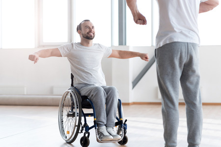 Attentive disabled man training in the gym with the orthopedist