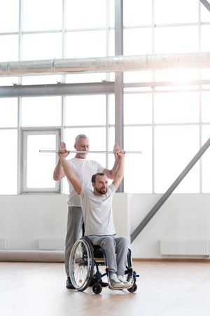 enable: Attentive physical therapist doing a morning gymnastics with his patient Stock Photo