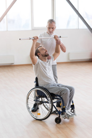 orthopedist: Serious aged general practitioner teaching the disabled in the gym Stock Photo