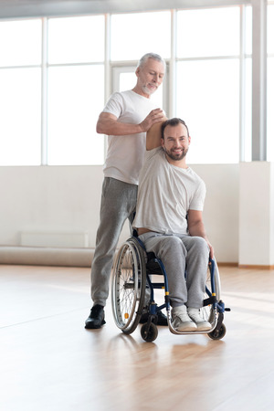 orthopedist: Proficient orthopedist exercising with a handicapped in the gym
