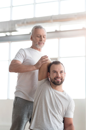enable: Concentrated aged orthopedist helping a handicapped in the gym Stock Photo