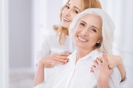 Ceerful aged woman embracing with her daughter Stock Photo