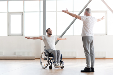 orthopedist: Handsome disabled man training in the gym with the orthopedist Stock Photo