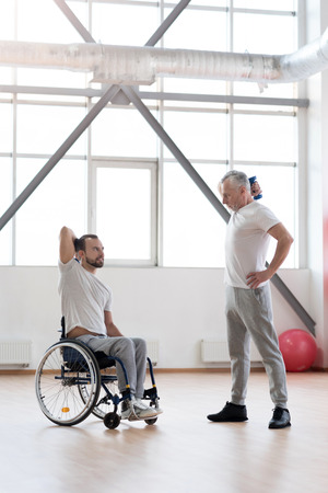 Athletic coach training the disabled young man in the gym