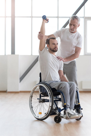 orthopedist: Athletic disabled man training with the coach in the gym Stock Photo