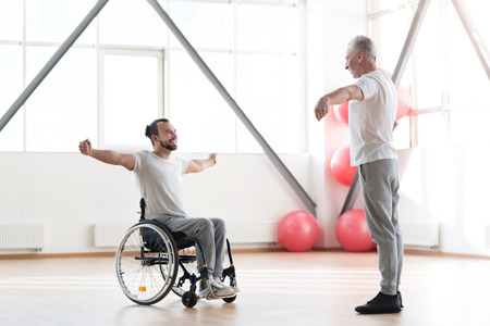 Delighted young disabled patient training with the orthopedist Stock Photo