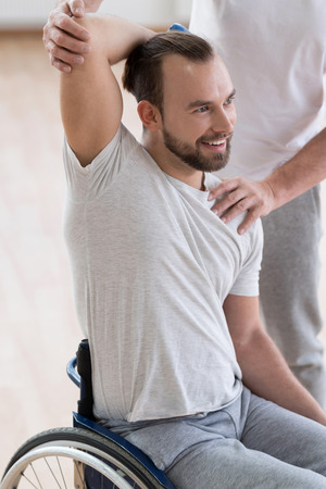 orthopedist: Amused young disabled man exercising in the gym
