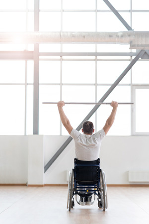 salud y deporte: Powerful young disabled man exercising in the gym