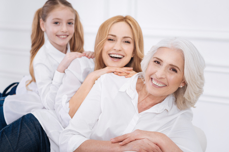 Cheerful family members sitting on the couch Stock Photo