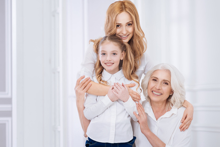 Loving beautiful woman embracing her little girl and senior mother Stock Photo