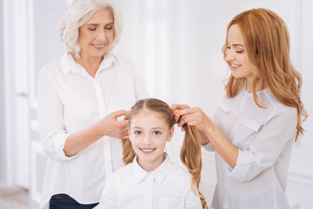 Positive family members making ponytails for little girl Stock Photo