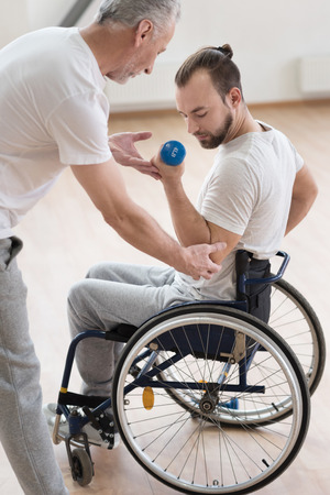 orthopedist: Involved disabled man exercising with his coach in the gym Stock Photo