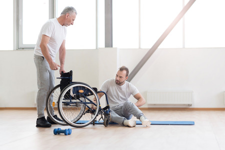 orthopedist: Involved orthopedist working with disabled patient in the gym