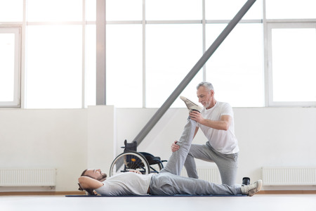 enable: Cheerful aged orthopedist working out with disabled patient