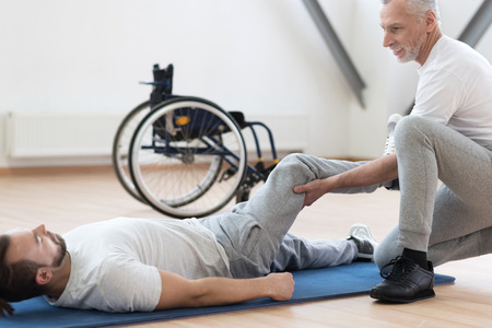 orthopedist: Charismatic orthopedist stretching the handicapped in the gym