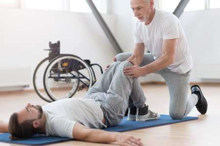 orthopedist: Skilled aged orthopedist stretching the disabled person in the gym Stock Photo