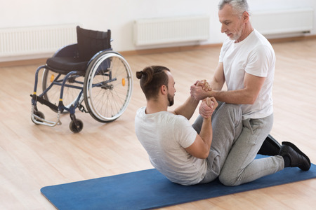 orthopedist: Skilled orthopedist assisting the disabled in the gym Stock Photo