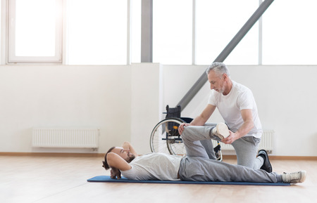 proficient: Proficient aged orthopedist working out with handicapped