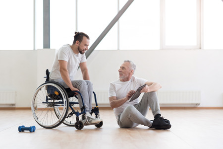 orthopedist: Cheerful orthopedist communicating with disabled patient in the gym
