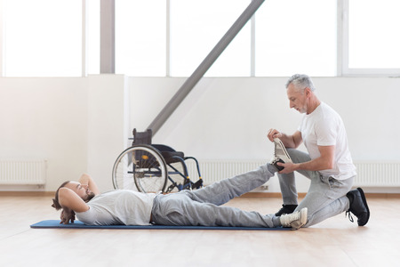 enable: Concentrated aged orthopedist helping with disabled patient