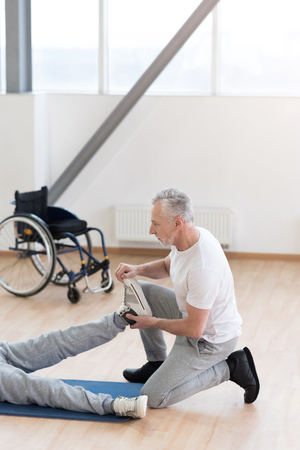 Attentive aged orthopedist helping the disabled patient in the gym